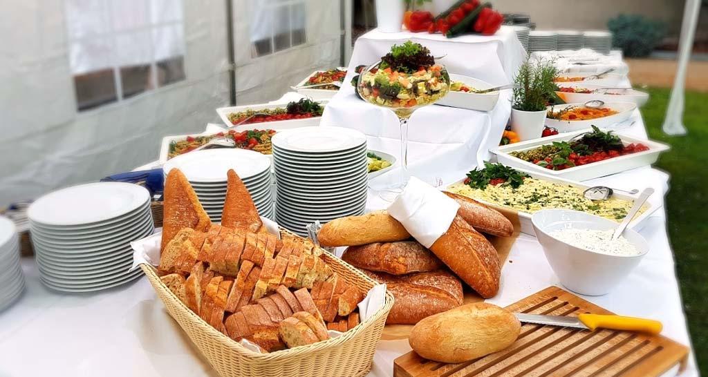 Buffet mit verschiedenen Brotsorten und weißem Geschirr